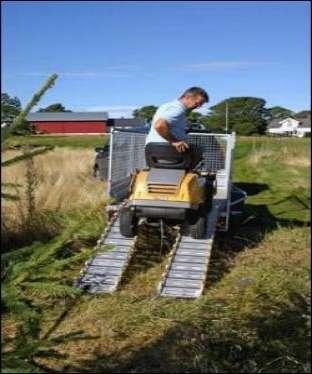 En kørerampe bruges til at køre en græsslåmaskine op på en trailer